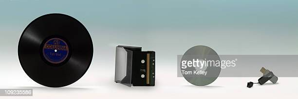 View of a variety of recording and information storage devices from left to right a vinyl record or album a cassette tape a compact disc or CD and a...