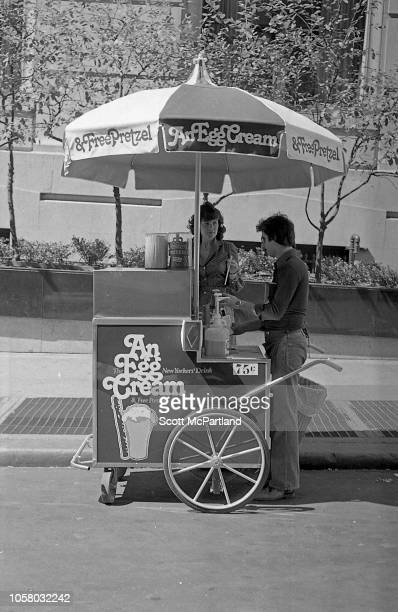 View of a vendor as he prepares an egg cream for a customer at his cart in lower Manhattan New York New York September 1980