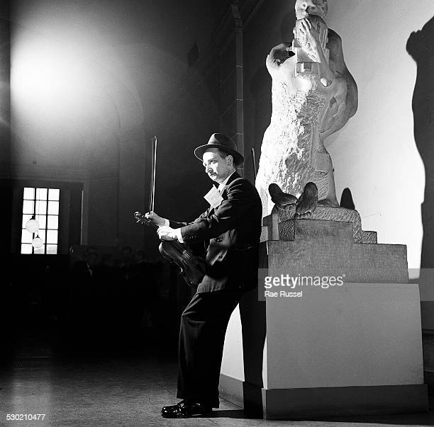 View of a violinist tuning his violin for a concert sponsored by WNYC radio and held at the Brooklyn Museum Brooklyn New York New York 1947