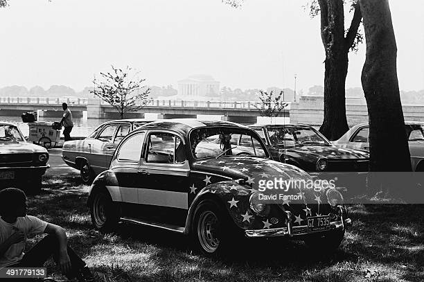 View of a Volkswagen Beetle painted in an American stars and stripes motif parked on the grass Washington DC circa 1970s