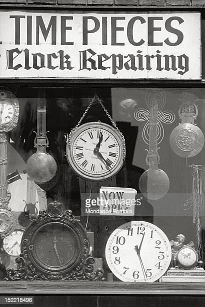 A view of a watchmaker's shop window whose sign 'Time pieces clock repairing' is put among antique clocks and grandfather clocks New York