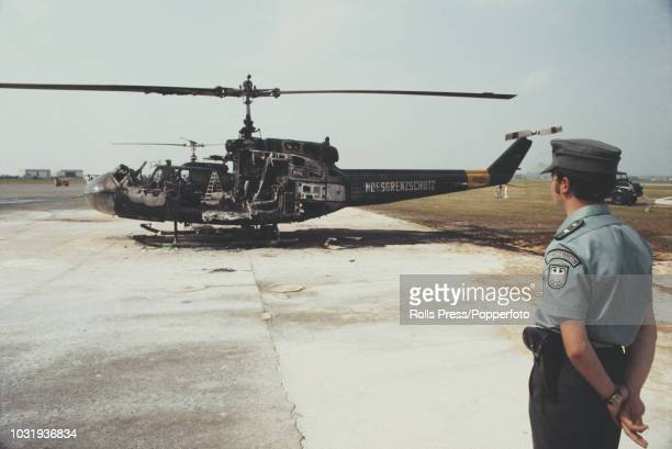 View of a West German Bundesgrenzschutz officer standing guard near a grenade damaged Bell UH-1 helicopter on the day after a gun battle between West...
