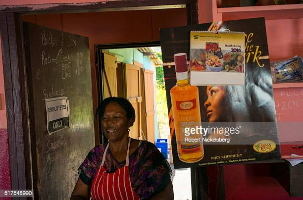 View of a woman as she cooks in her restaurant Hillsborough Carriacou island Grenada February 25 2016 The poster on the wall advertises the local...