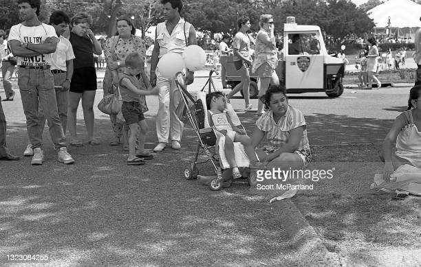 View of a woman crouched on the grass beside a toddler sleeping in a stroller in Flushing Meadows Park, in the Corona neighborhood, Queens, New York,...