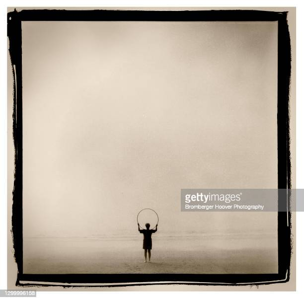 View of a woman holding a hoop aloft as she stands on the sands at Rockaway Beach, Oregon, 1999.