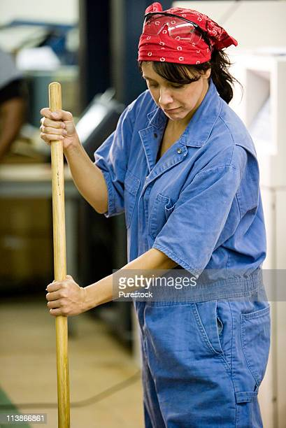 View of a woman in coveralls sweeping the floor in a warehouse