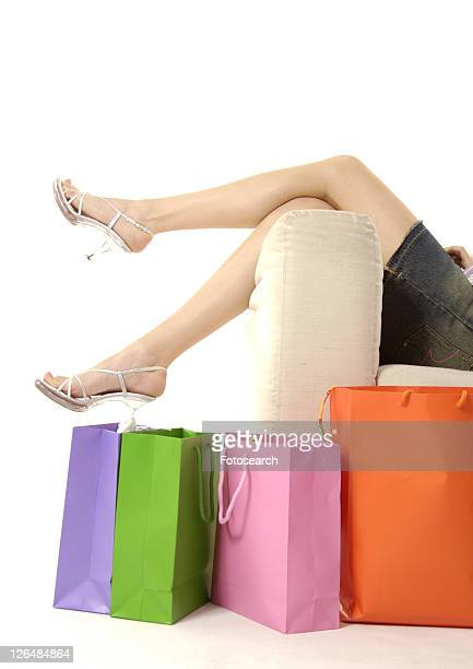 View of a woman lying on a couch with shopping bags placed beside it.