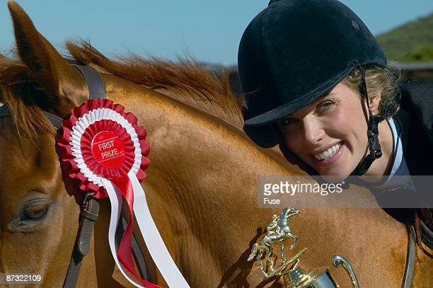 View of a woman resting her head on a horse?s neck and smiling while holding a trophy