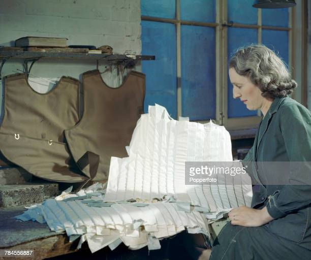 View of a woman seamstress making armoured waistcoats for Royal Air Force airmen and pilots in a factory in the United Kingdom in July 1943