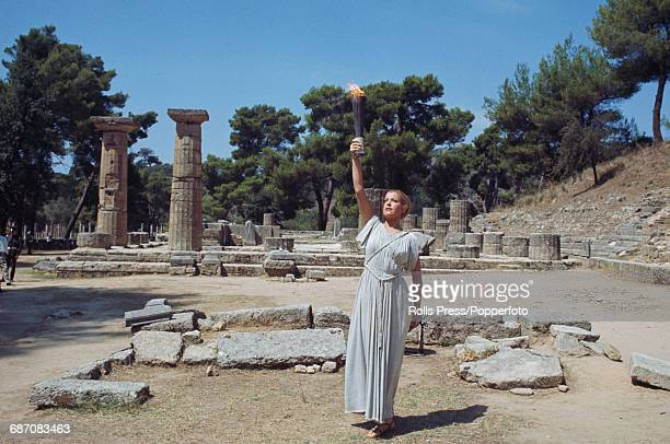View of a woman wearing a ancient greek style chiton tunic representing a vestel virgin standing and raising a torch with the Olympic flame at the...