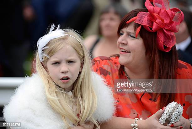 View of a woman wearing a fascinator with a young girl in a fake fur wrap at the Investec Ladies Day race meeting at Epsom Downs racecourse in Epsom...