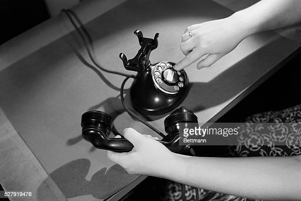 A view of a woman's hands dialing a rotary telephone Undated photograph