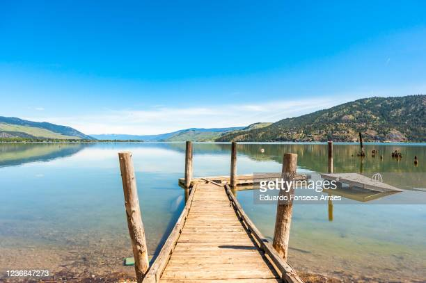view of a wood pier, the lake okanagan reflecting the mountains, against a sunny clear blue sky. - okanagan valley stock pictures, royalty-free photos & images