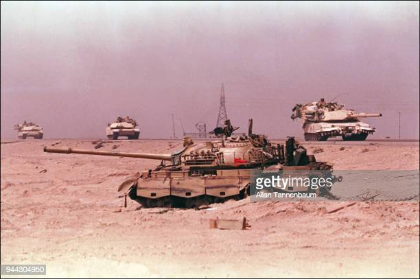 View of a wrecked Iraqi Type 69II Main Battle Tank abandoned beside a road as American M1A1 Abrams tanks drive past after the liberation of Kuwait...