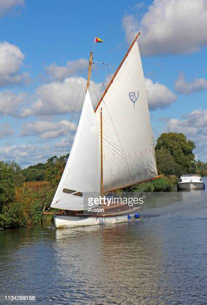 A view of a yacht sailing on the River Ant on the Norfolk Broads near How Hill Ludham Norfolk England United Kingdom