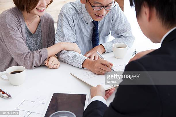 View of a Young attractive couple signing contract