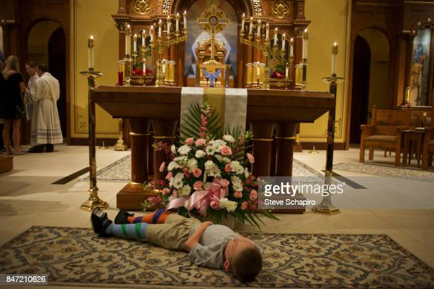 View of a young boy both his legs in casts as he lies down in front of an altar during a healing service at an unspecified church Columbus Ohio 2016