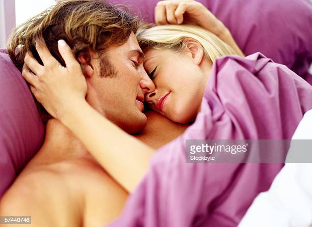 view of a young couple in bed holding each other - romantic young couple sleeping in bed stock photos and pictures