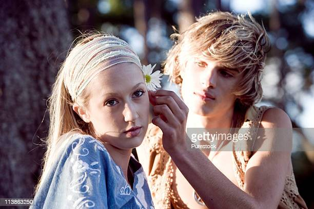 View of a young couple in vintage 1960's hippie, putting flower behind ear