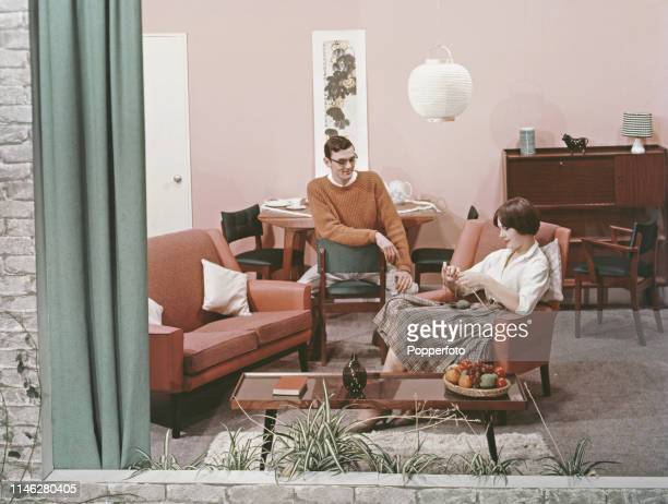 View of a young couple seated in the living room of a modern house the young woman seated in an armchair knitting with the man seated at a dining...