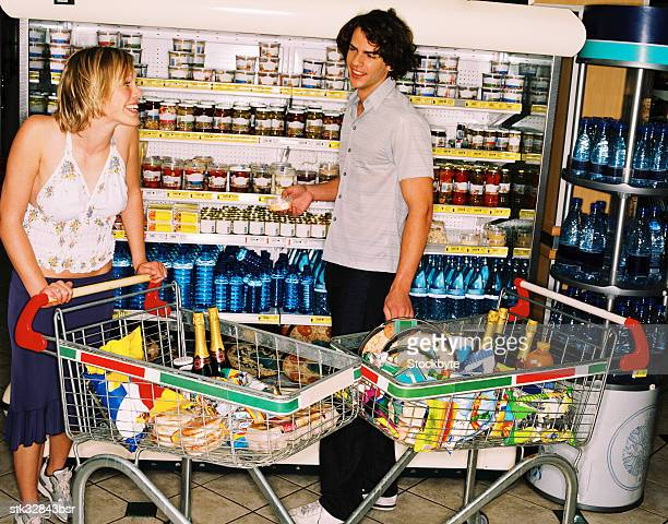 view of a young couple shopping with two shopping carts