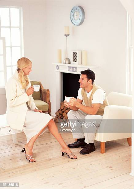 view of a young couple sitting with cups of coffee - white skirt stock pictures, royalty-free photos & images