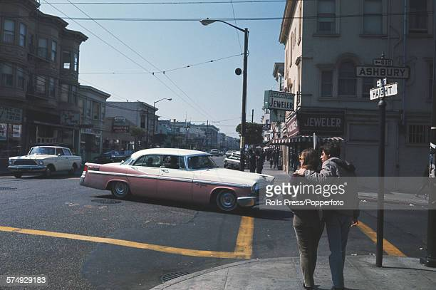 View of a young couple standing together on a sidewalk by the intersection of Haight and Ashbury streets in the HaightAshbury district of San...