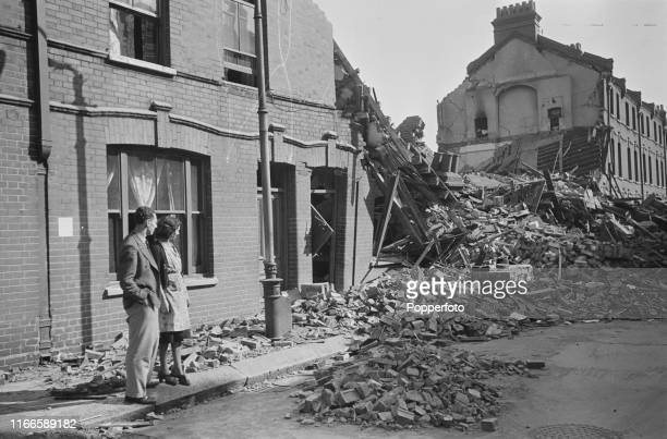 View of a young couple standing together on the pavement as they survey damaged and wrecked terraced houses in their residential street after a...
