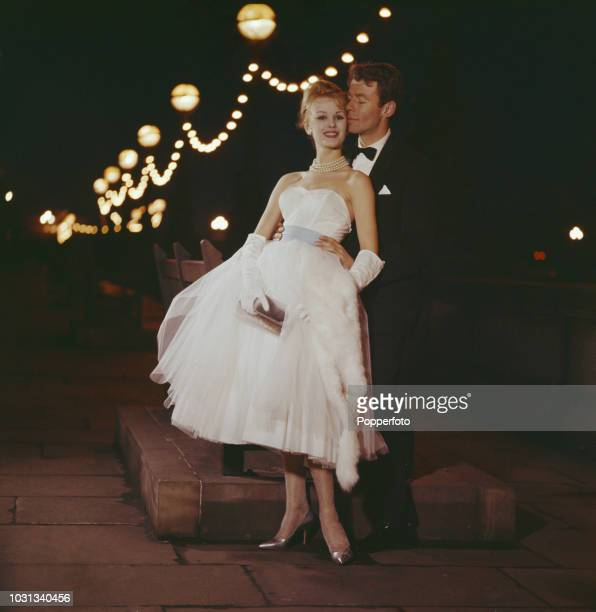 View of a young couple the woman wearing white ballgown with strapless top and long white gloves the man wearing an evening suit as they pose...