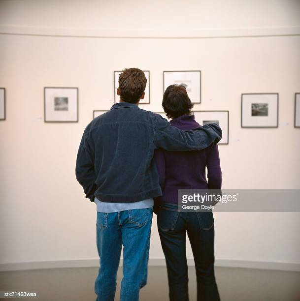 view of a young couple viewing art hung on the wall in a gallery