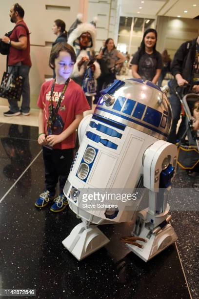 View of a young fan posed beside an 'R2D2' android at the Star Wars Celebration event at Wintrust Arena, Chicago, Illinois, April 13, 2019.