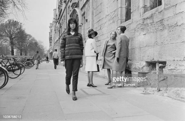 View of a young female Oxford University student dressed in Beatnik clothing walking past three more traditionally dressed students, Caroline...