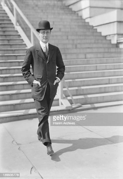 View of a young Franklin Delano Roosevelt strolling down the street wearing a derby or bowler hat early twentieth century