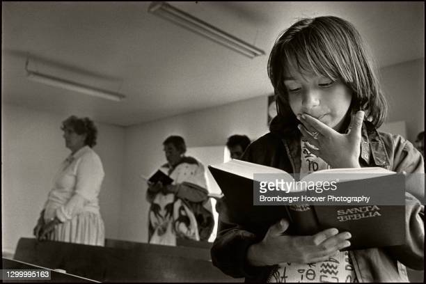 View of a young girl as she reads a Spanish-language bible during a church service, Tijuana, Mexico, 1990.