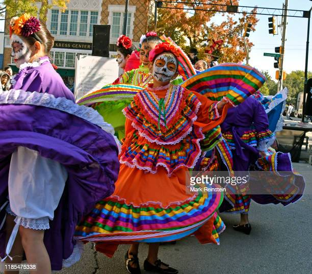 View of a young girl in a traditonal la Calavera Catrina outfit and facepaint as she dances with similarly costume others during the Day of the Dead...