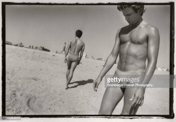 View of a young man dressed in a swim brief-style swimsuit as he stands on the sand at Zuma Beach, Los Angeles, California, 1986. Another man in a...