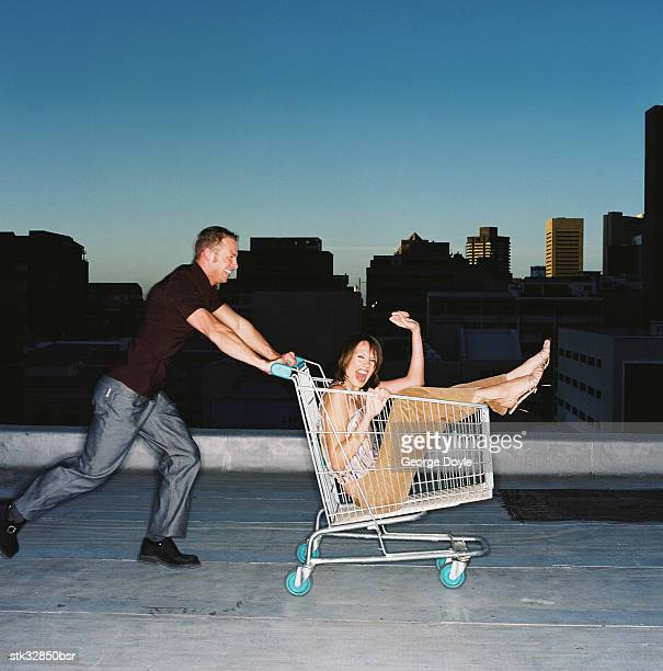 view of a young man pushing a young woman in a shopping cart