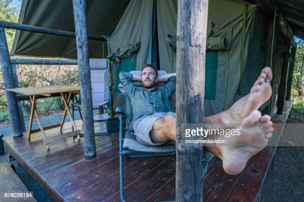 Vue d'un jeune homme détente devant sa tente
