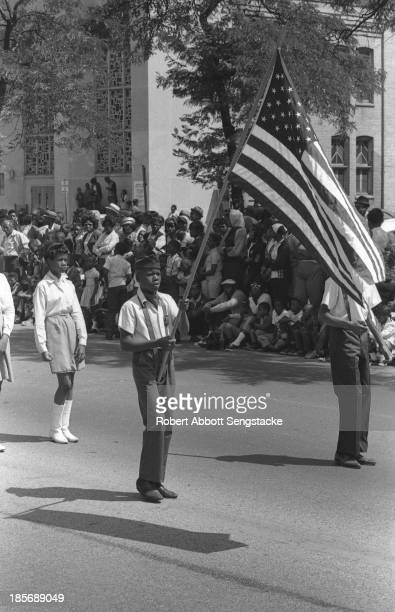 View of a young student carrying an American flag as he marches with his high school band, during the Bud Billiken Day parade, Chicago, Illinois, mid...