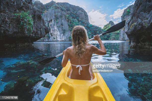 view of a young woman canoeing in beautiful tropical lagoon - el nido stock pictures, royalty-free photos & images