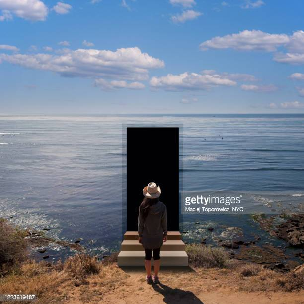view of a young woman on the beach facing a door open in the landscape. - junge frau rätsel stock-fotos und bilder