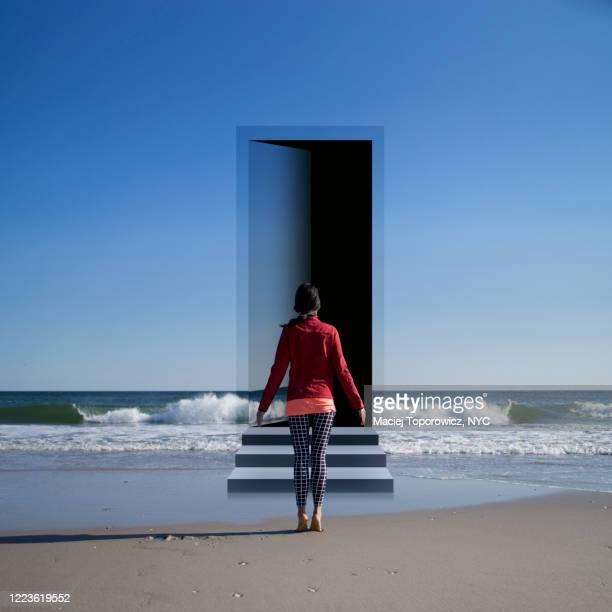 view of a young woman on the beach facing a door open in the landscape. - imagination photos et images de collection