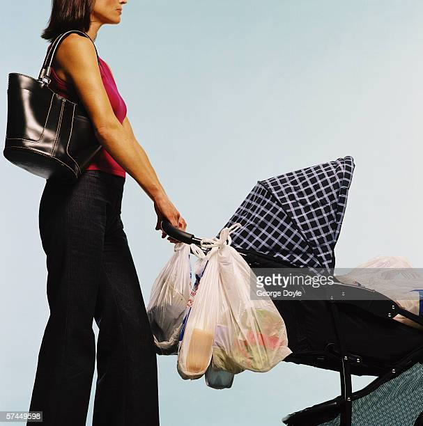 view of a young woman pushing a baby pram with grocery bags attached