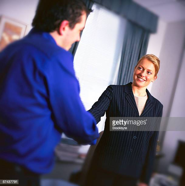 view of a young woman shaking a young man's hand