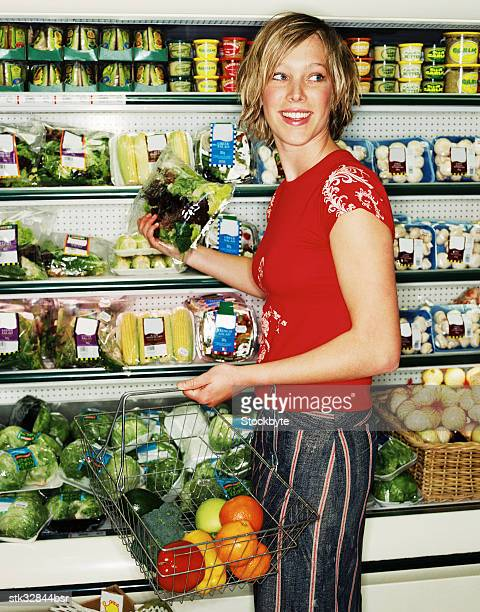 view of a young woman shopping for vegetables with a shopping basket
