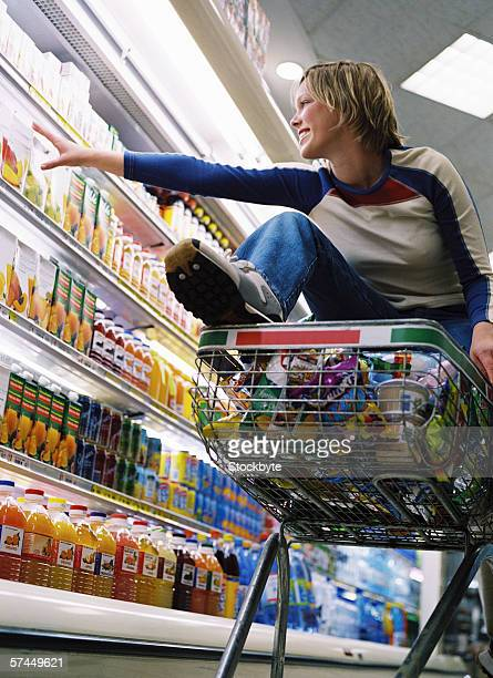 view of a young woman sitting in a shopping cart reaching out for a product
