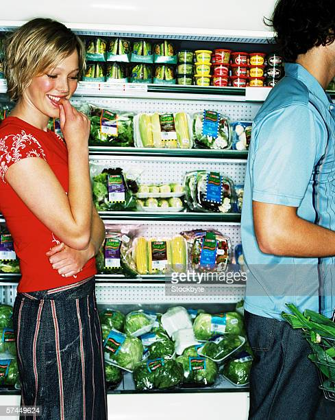 view of a young woman standing in front of a vegetable display freezer