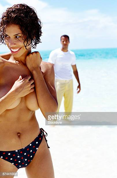 view of a young woman standing topless on the beach with young man in background