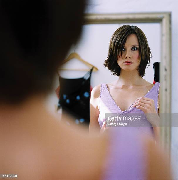 view of a young woman trying out a dress in front of a mirror