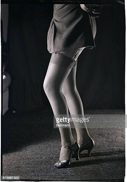 A view of a young woman's legs She wears a skirt short enough to reveal her thigh high stockings Ca 19401955